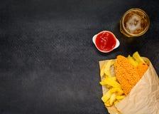 Patate fritte e pesce sullo spazio della copia con birra Immagini Stock
