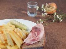 Patate fritte e un vetro di vodka Fotografia Stock