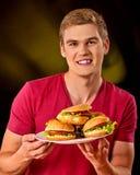 Patate fritte ed hamburger mangiatori di uomini sulla tavola Fotografia Stock Libera da Diritti