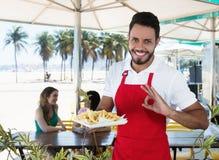 Patate fritte felici del servizio del cameriere alla barra della spiaggia fotografia stock libera da diritti