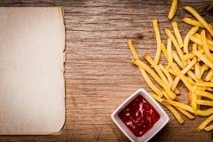 Patate fritte, ketchup e carta su una tavola di legno Fotografie Stock Libere da Diritti