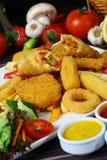 Patate fritte miste, strisce del pollo, anelli di cipolla Immagine Stock