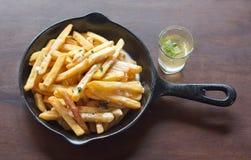 Patate fritte nella pentola sulla tavola con salsa Immagini Stock