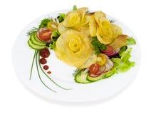 Patate fritte sotto forma di rosa su una zolla con un'insalata su wh Immagine Stock