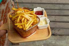 Patate fritte in un setaccio disposto su un vassoio di legno fotografie stock