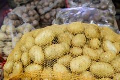 Patate nelle borse della maglia da un mercato Fotografie Stock