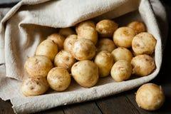 Patate novelle con la buccia sulla tavola in una borsa Fotografie Stock