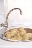 Patate in un lavandino di cucina Immagini Stock Libere da Diritti
