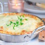 Patate smerlate kitsch o gratin della patata in piatto bollente, holid immagini stock