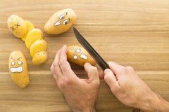 Patate spaventose del fronte che sono tagliate su un bordo di legno della cucina Immagine Stock