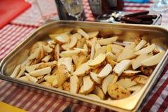 Patate tagliate fresche su uno strato di cottura del metallo Fotografia Stock Libera da Diritti
