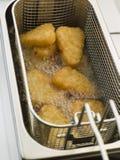 Patate tritate che sono fritte nel grasso bollente in olio di mais Fotografie Stock