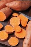 Patates douces fraîches entières et coupées en tranches sur le panneau en bois de cuisine d'en haut Aliment biologique Photo libre de droits