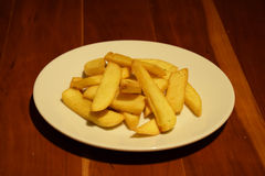 Patatine fritte dorate in piatto bianco sulla tavola di legno Immagine Stock Libera da Diritti