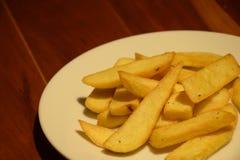 Patatine fritte dorate in piatto bianco sulla tavola di legno Immagini Stock Libere da Diritti