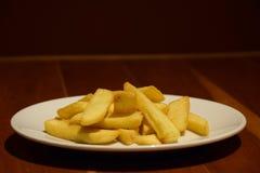 Patatine fritte dorate in piatto bianco sulla tavola di legno Fotografia Stock