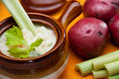 Patatoe soup in crock with celery spoon. The crock of patato soup with celery spoon, accompanied by patatoes and celery sticks Stock Image