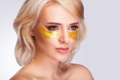 Patch Under Eyes. Beautiful Woman Face With Gold Hydrogel Patches, Lifting Anti-Wrinkle Collagen Mask On Fresh Healthy Facial Ski stock photography