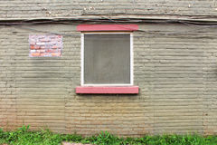 Patched green painted old brick wall with window centered. Horizontal view stock photos