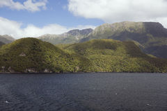 Patches of sun and shadow on the mountains around Dusky Sound Stock Photos