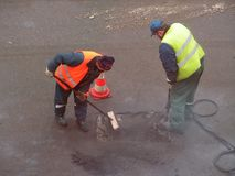 Patching the hole. Road mender at work; teamwork, hard work, power, blue-collar concept stock image