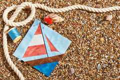 Patchwork block, spool of thread, pin cushion and rope lie on sea stones of beach Stock Photos