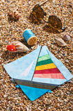 Patchwork block, spool of thread, pin cushion and sunglasses lie on sea stones of beach Royalty Free Stock Image
