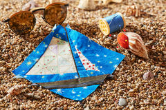 Patchwork block, spool of thread, pin cushion and sunglasses lie on sea stones of beach Royalty Free Stock Photo