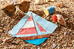 Patchwork block, spool of thread, pin cushion and sunglasses lie on sea stones of beach Stock Photo