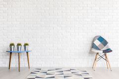 Patchwork can be stylish, too!. Shot of a modern room with a patchwork chair and a table with cactuses Stock Images