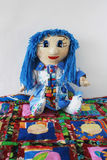 Patchwork doll quilt rug. Patchwork doll with blue hair sitting on a cheerful patchwork rug Stock Photos