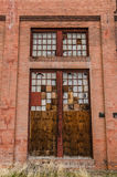 Patchwork Doors. Huge doors in an old, historic building with broken glass and wood making a patchwork design where the windows once were Stock Images