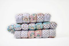 Patchwork and fashion concept - beautiful stack of colorful quilts, bedspreads stacked in several rows in height for storage, sale. Of stitched products on a Stock Photos