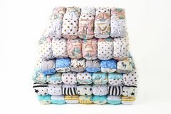 Patchwork and fashion concept - beautiful stack of colorful quilts, bedspreads stacked in several rows in height for storage, sale. Of stitched products on a Royalty Free Stock Image