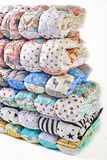 Patchwork and fashion concept - beautiful stack of colorful quilts, bedspreads stacked in several rows in height for storage, sale. Of stitched products on a Royalty Free Stock Photo