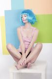 Patchwork. Funky Girl in Azure Wig Sitting in Studio on White Chair. Fancy Girl in Azure Wig Sitting in Studio Royalty Free Stock Image