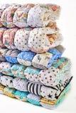 Patchwork i mody pojęcie - piękna sterta kolorowe kołderki, bedspreads brogujący w kilka rzędach w wzroscie dla magazynu, sprzeda Zdjęcie Royalty Free
