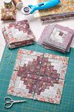 Patchwork log cabin blocks on craft mat, stack of blocks, sewing accessories stock photography
