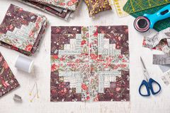 Patchwork log cabin blocks, stack of blocks, sewing accessories on white wooden surface royalty free stock images