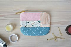 Patchwork mini pouch, golden hairpins and lip balm royalty free stock image