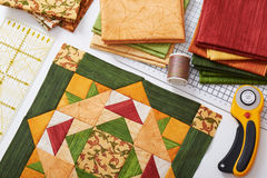 Patchwork orange-green block, quilting fabrics, sewing accessories Stock Photo