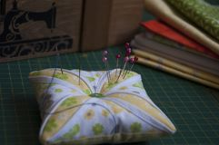 Patchwork pin cushion. With needles royalty free stock photos