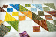 Patchwork Quilt Assembly. Patchwork quilting being assembled with mischellaneous fabric squares Stock Photography