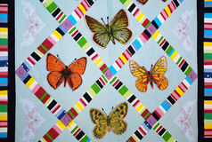 Patchwork quilt with butterflies. Colorful patchwork quilt with butterflies. Handmade work Royalty Free Stock Photo