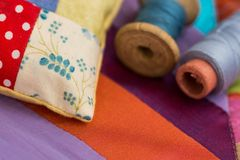 Patchwork, quilting, sewing, tailoring and fashion concept - close-up on beautiful colorful stitched cushion and threads. In spools, macro on a pillow with royalty free stock photo