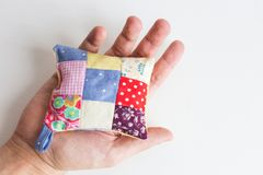 Patchwork, quilting, sewing, tailoring and fashion concept - close-up on beautiful colorful stitched pincushion in human Royalty Free Stock Images