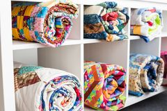 Patchwork, sewing and fashion concept - white bookcase with six shelves and bright finished quilts in the studio, the Royalty Free Stock Photography