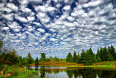 Patchwork Sky Over Country Pond. Quilted clouds over a small pond. The trees are reflected in the calm water Royalty Free Stock Photo