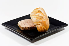 Pate and bread. Pate and half a baguette on a black square  plate Royalty Free Stock Photos