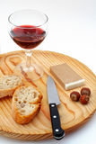 Pate, bread, glass of red wine, hazelnuts and knife on wood plate Stock Photo